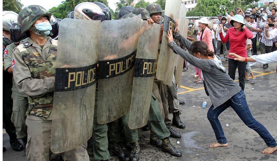 Une jeune cambodgienne manifeste sa colère face aux policiers anti-émeutes devant la mairie de Phnom Penh. Les habitants de Boueng Kak protestent contre un projet de développement chinois autour du lac.