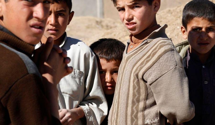 Des enfants afghans observent une patrouille de soldats américains à Muhammad Aghah, dans la province de Logar, dans l'est de Afghanistan.