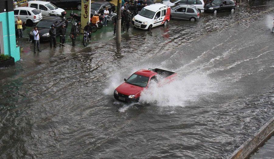Une voiture traverse une avenue de Rio, inondée après que le Brésil a été frappé par des pluies torrentielles vendredi.