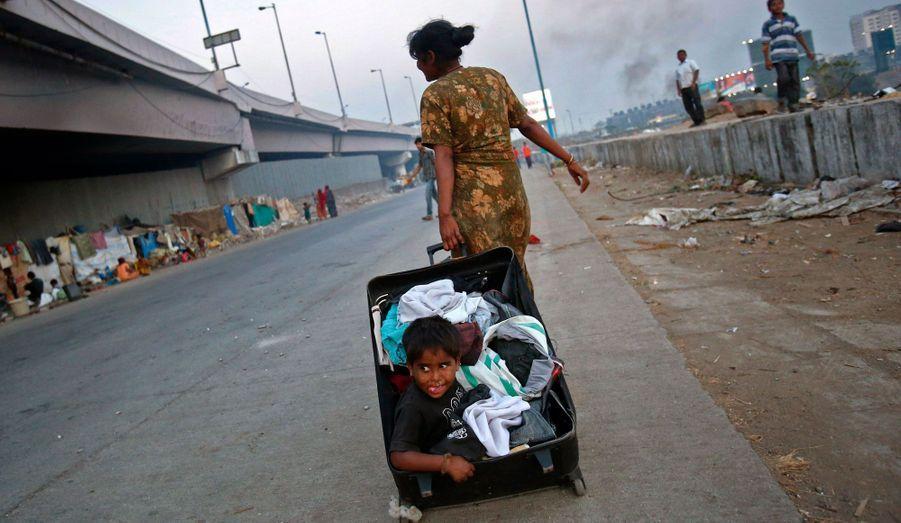 Riaz, trois ans, est dans une valise ouverte remplie de vêtements que sa mère traîne, le long d'une autoroute, à Mumbai.