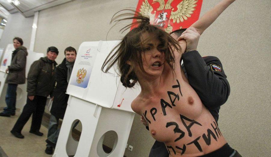 Des activistes de l'organisation ukrainienne Femen ont envahi dimanche le bureau de vote dans lequel Vladimir Poutine a déposé son bulletin dans l'urne. Sur le corps de la jeune femme, un message proclame: «Je vole pour Poutine.»