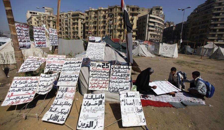 Des manifestants anti-Morsi et des écoliers écrivent des slogans sur des pancartes, Place Tahrir, au Caire. Ils rejettent l'autorité du président actuel et l'influence des Frères Musulmans.