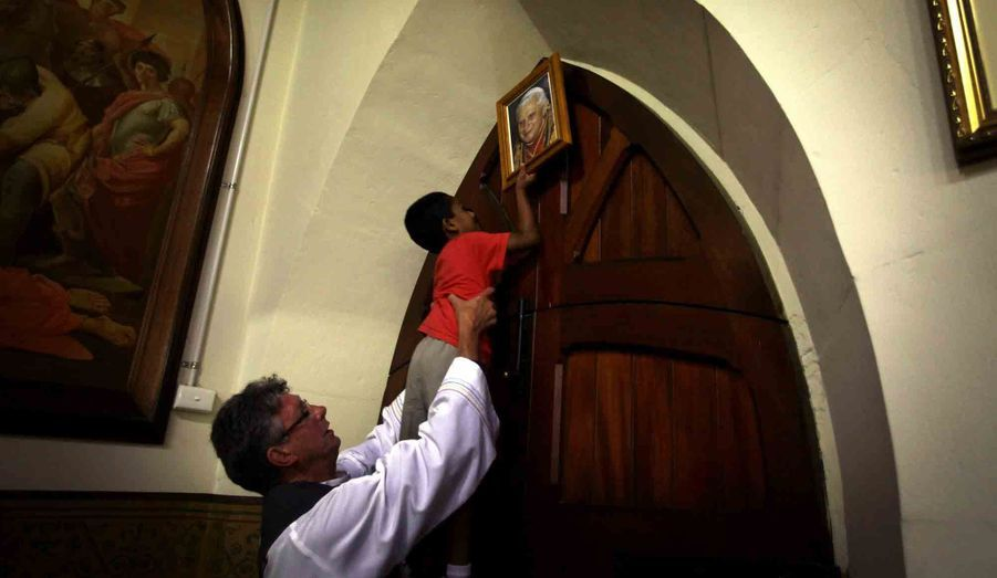 Le père Garry McKeown aide un petit garçon à retirer le portrait de Benoît XVI qui trône sur un mur de l'église catholique Sainte Marie de la ville de Mudgee (Australie). Le pontificat de Benoît XVI s'est terminé jeudi 28 février à 20 heures.