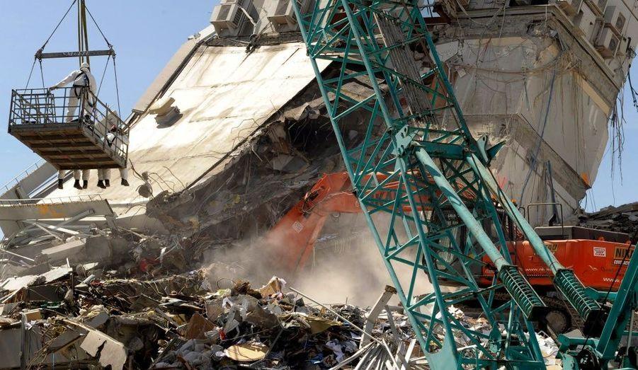 Une équipe de secouristes venue de Grande-Bretagne, devant les ruines de l'immeuble Pyne Gould, à Christchurch. La population s'apprête à enterrer les premières victimes du séisme ce lundi, une semaine après la catastrophe qui a fait au moins 148 victimes selon le dernier bilan communiqué par les autorités.