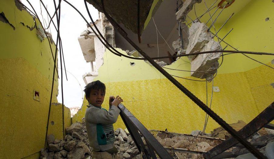 Un petit garçon libyen passe du temps dans sa maison détruite de Sirte.