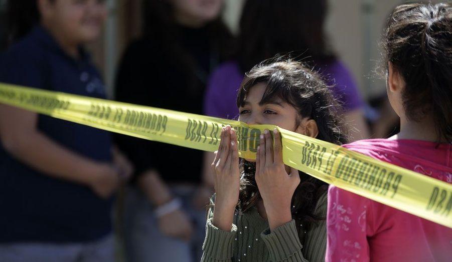 Une petite fille joue avec un ruban délimitant une scène de crime à Monterrey, au Mexique, dimanche. Cinq dealers présumés ont été abattus lors d'une fusillade.