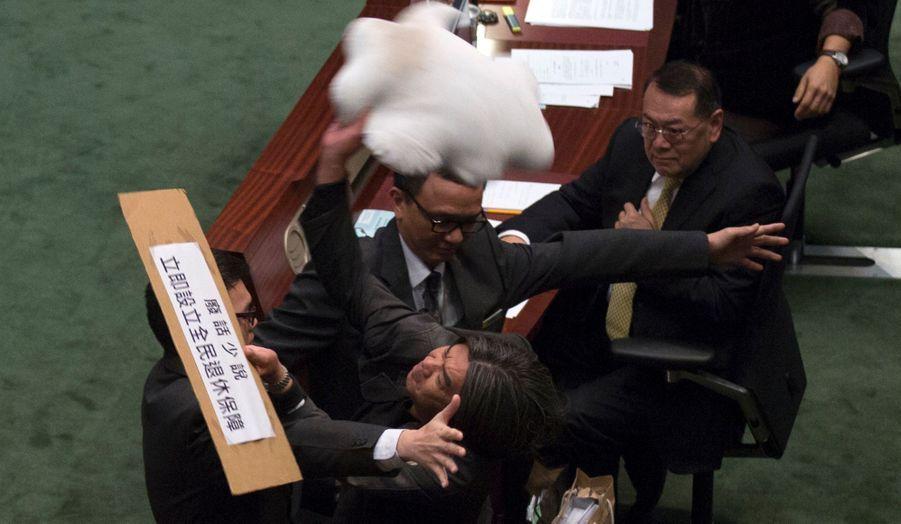 Le député Leung Kwok-hung lance un coussin en forme de nuage vers le secrétaire aux Finances de Hong Kong, John Tsang, à qui il demande un plan de retraite pour tous.