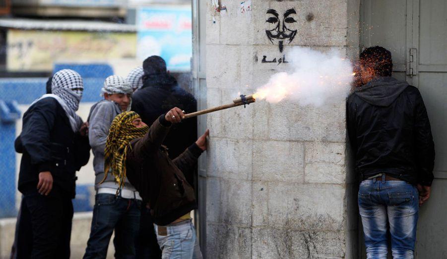 Un manifestant palestinien utilise une arme de fortune pour tirer des pétards alors qu'un autre manifestant se met à couvert lors d'affrontements avec les soldats israéliens et les gardes frontières dans la ville d'Hébron. Dimanche, Israël a exigé de l'Autorité palestinienne d'endiguer une vague de protestations anti-israéliennes avant la visite du président américain Barack Obama dans la région le mois prochain. La mort d'un détenu palestinien dans une prison israélienne et une grève de la faim par quatre détenus alimentent les tensions en Cisjordanie.