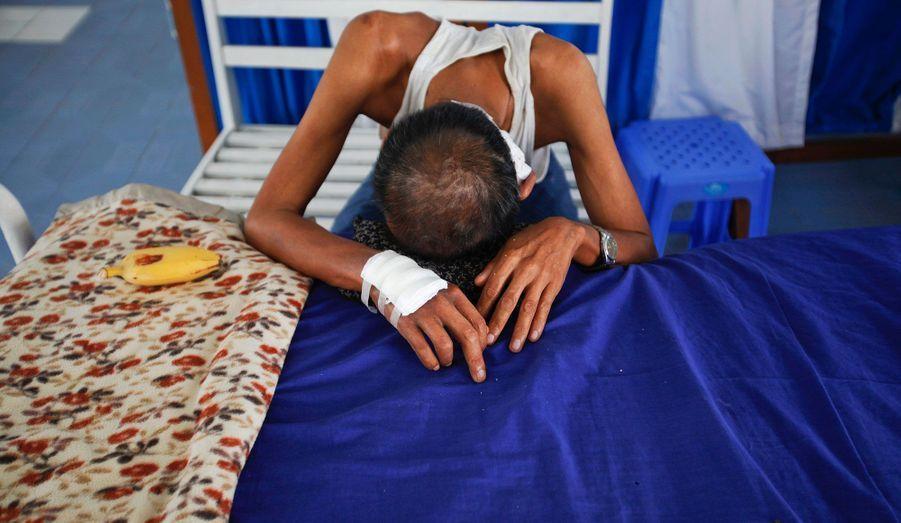 Un malade atteint d'un cancer est allongé sur son lit d'hôpital dans la banlieue de Yangon, à la fondation de U Hla Tun Hospice, en Birmanie. La fondation, créée en 1998, accepte les patients cancéreux rejetés par les hôpitaux publics en phase terminale et propose de soulager leurs symptômes. Le coût de prise en charge est très élevé pour les hôpitaux publics dans le cas de maladies graves, et les patients sont évacués lorsque le traitement est terminé. Ils ne reçoivent pas assez de soins à cause de la surpopulation dans les salles de cancérologie.