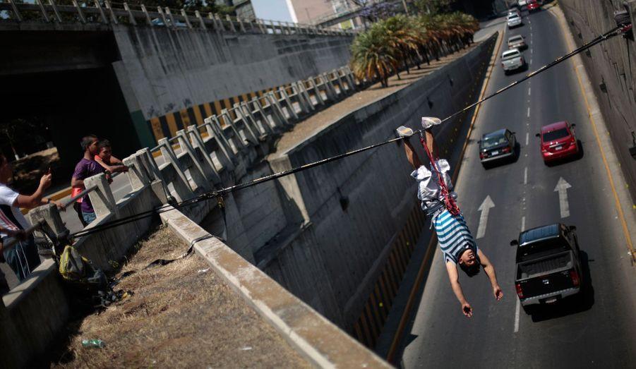Luis Amezquita est pendu à l'envers sur l'avenue Periferico lors d'un exercice de slackline dans la ville de Guatemala. Selon Amezquita, c'est la première fois au Guatemala que quiconque tente de pratiquer le slackline dans la rue. C'est un sport extrême qui exige un équilibre parfait.