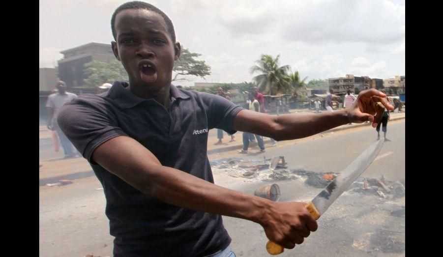 Un militant anti-Gbagbo manifeste, un couteau à la main, dans les rues d'Abidjan. Les forces de sécurité ivoiriennes ont tué sept militantes, et les Nations Unies évaluent à 365 le nombre de morts depuis les élections disputées.