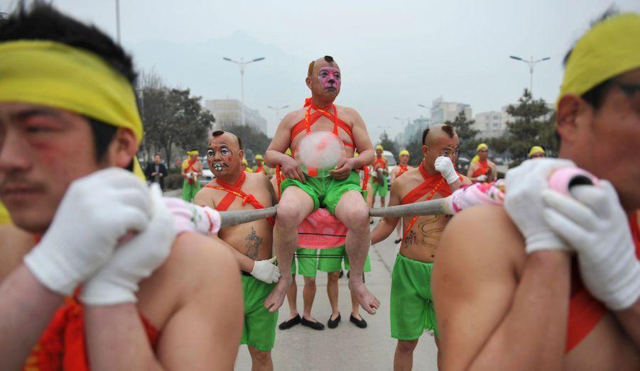 Un artiste porte un morceau de glace alors qu'il est assis sur une chaise à porteurs. Ce spectacle est réalisé par des artistes pour célébrer la fête des Lanternes dans une rue de Yongji, dans la province de Yongji. La Fête des Lanternes, qui tombe le 24 Février, a lieu le 15e jour du Nouvel An lunaire chinois et marque la fin de la Fête du Printemps.