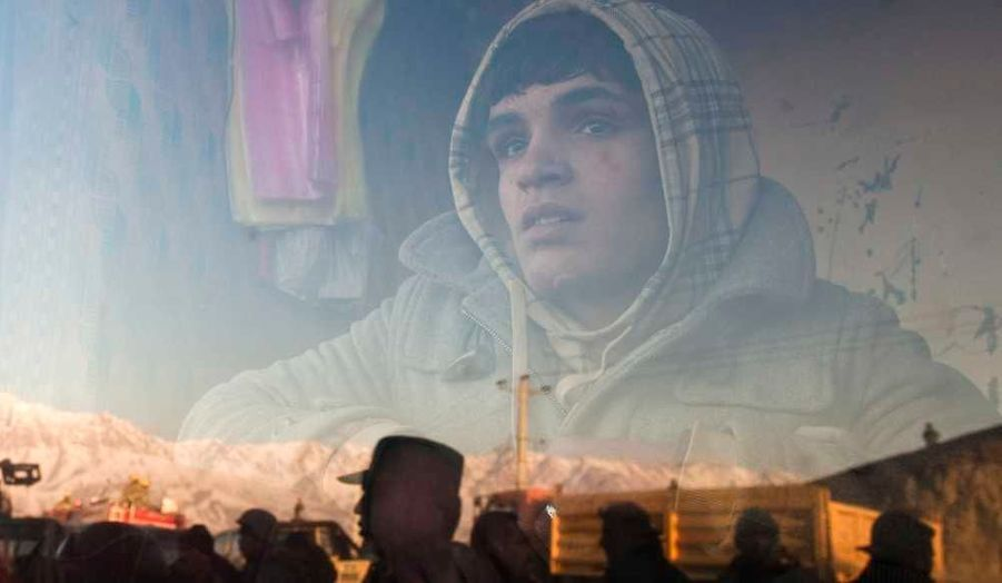 Un garçon afghan qui travaille dans une boulangerie regarde une protestation par la fenêtre. Douze personnes ont été tuées vendredi dans la journée la plus sanglante depuis que des manifestations anti-américaines ont éclaté mardi dernier en Afghanistan, après l'incinération d'exemplaires du Coran dans la plus grande base militaire américaine du pays.