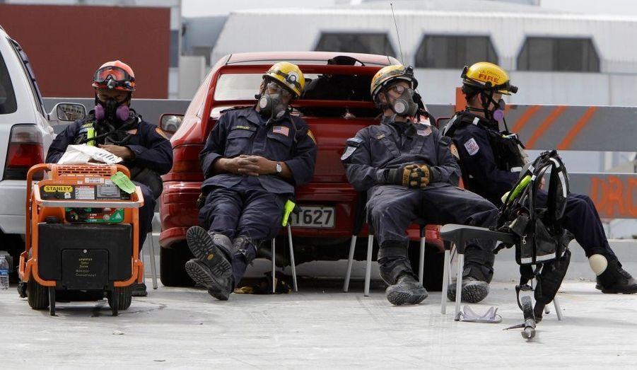 Des pompiers néozélandais prennent une pause dans leurs recherches de corps, dans un immeuble détruit de Christchurch, la deuxième plus grande ville du pays. Le bilan a officiellement atteint 155 morts après le séisme de la semaine dernière.