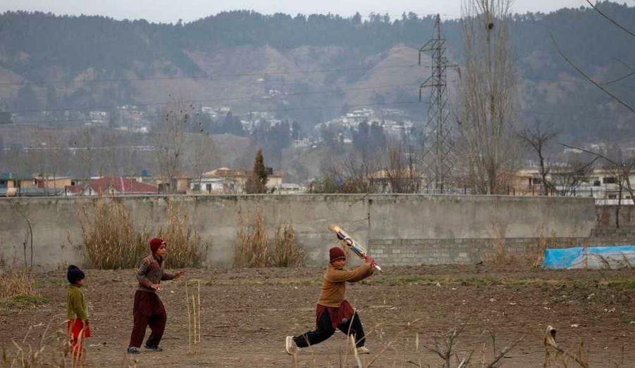 Des enfants jouent au cricket devant l'ex-emplacement de la maison où l'ancien chef d'Al Qaïda Oussama ben Laden a été tué, à Abbottabad au Pakistan. Le bâtiment a été entièrement rasé dans la nuit de samedi à dimanche.