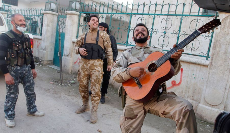 Des membres de l'Armée Syrienne Libre chantent et jouent de la guitare près de l'aéroport militaire à Alep. Un moment de légèreté entre les combats.