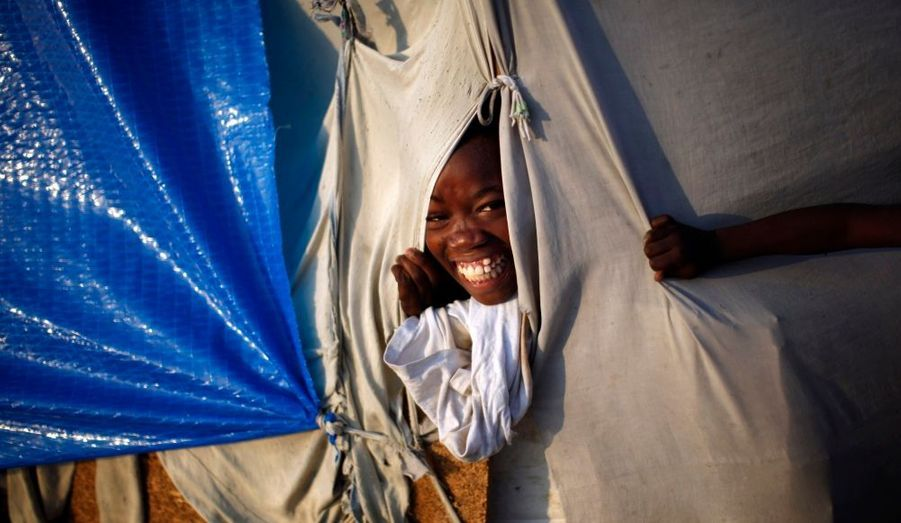 Une petite fille sourit, dans une tente d'un campement de rescapés à Port-au-Prince, où elle vit depuis le terrible séisme qui a ravagé Haïti le 12 janvier dernier.