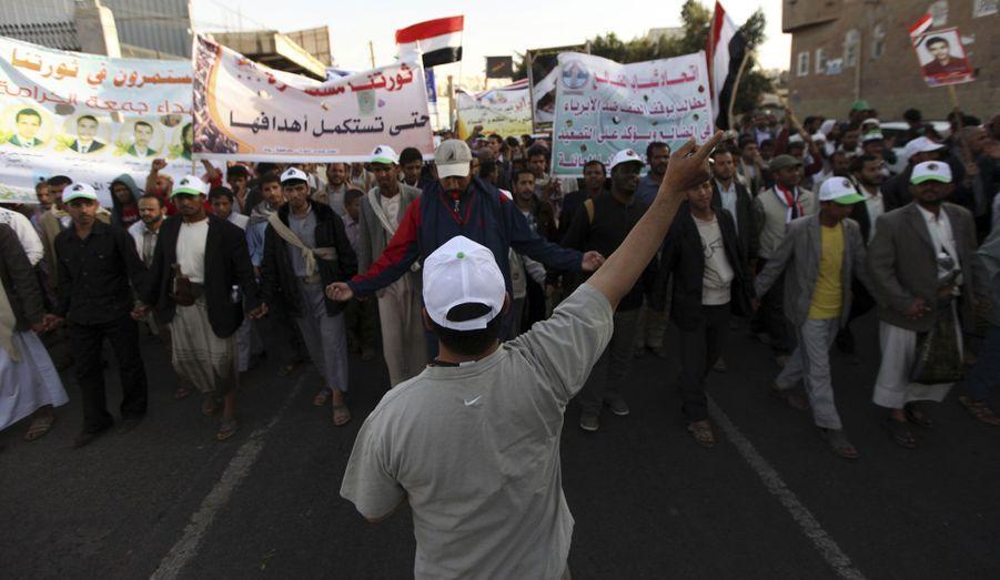 Des manifestants yéménites protestent dans la rue pour demander que l'ancien président, Ali Abdullah Saleh, soit jugé.