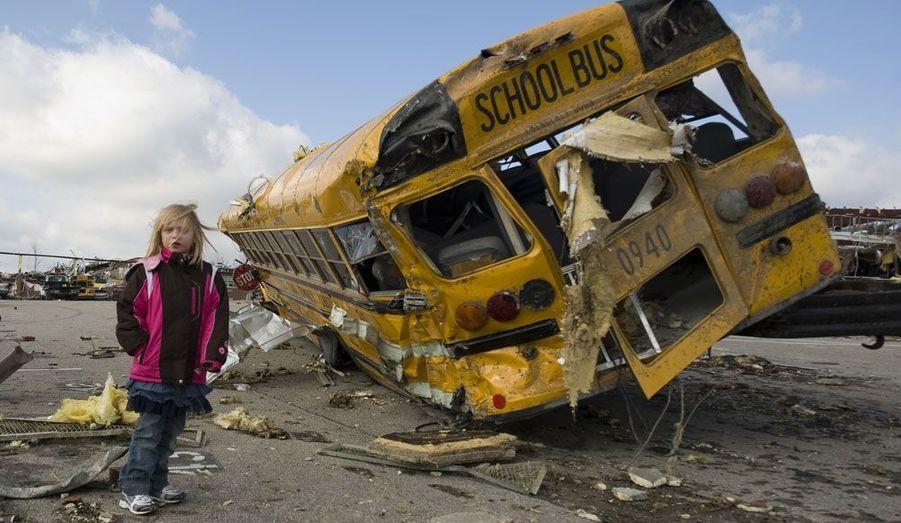 La petite Madeline Evans marche à côté d'un bus scolaire détruit par une tornade à Henryville, dans l'Indiana.