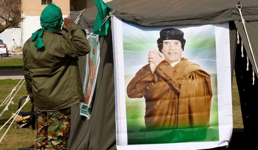 Un homme salue un portrait du leader libyen Mouammar Kadhafi près d'un barrage à Tripoli. Lundi, les forces de sécurité ont tiré en l'air pour disperser les militants anti-Kadhafi dans le quartier de Tadjoura, à l'est de la capitale.