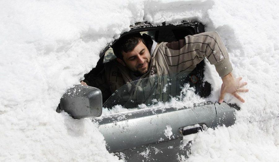 Un homme enlève la neige qui recouvre sa voiture après une tempête dans la région d'Aley, située à l'est du Liban.