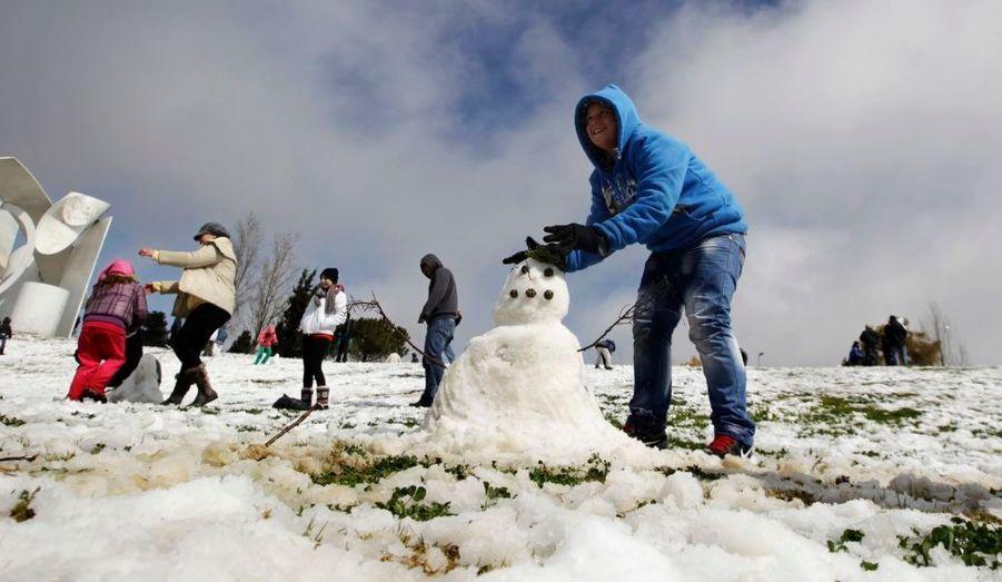 Un enfant construitun bonhomme de neigedans un parcà Jérusalem.Pour la première fois depuis quatre ans, il a neigé sur la ville, contraignant les établissements scolaires à fermer pour la journée de vendredi, selon les médias locaux.
