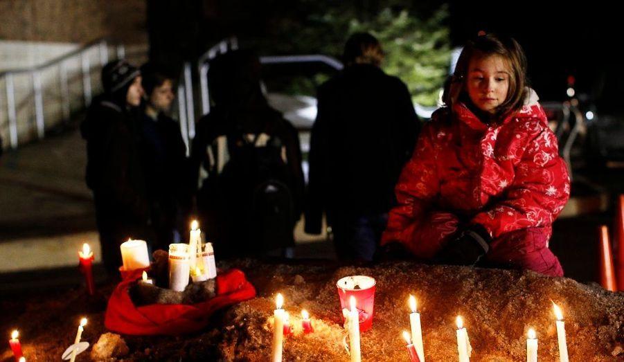 Une fillette se recueille sur un monticule de neige, devant l'église St. Mary. La fusillade qui a éclaté lundi dans le lycée Chardon High School a fait trois morts parmi les élèves, victimes de l'un de leurs camarades dont le mobile reste mystérieux.