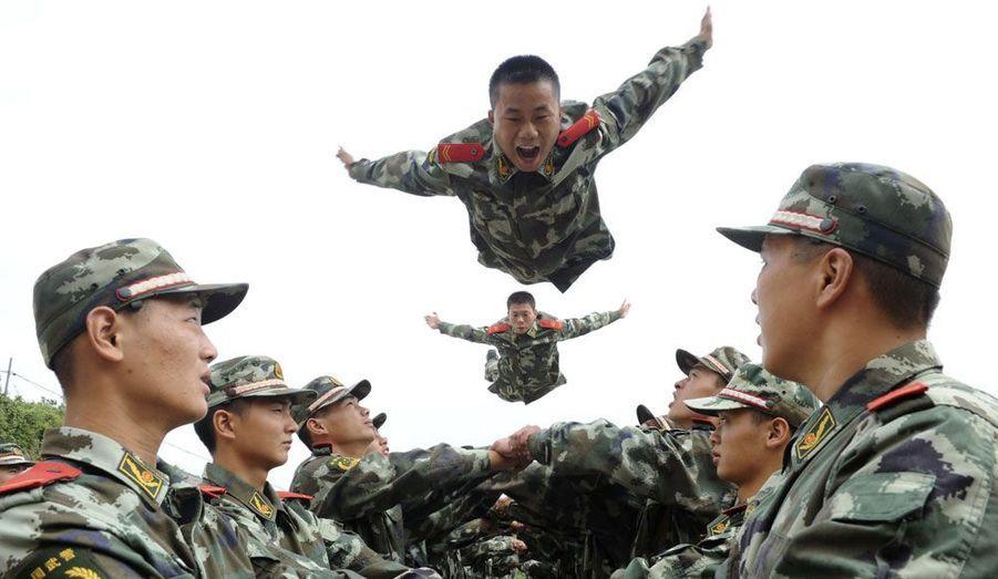Un groupe de paramilitaires font sauter leurs collègues lors d'un entraînement psychologique dans la ville de Tongling, en Chine.