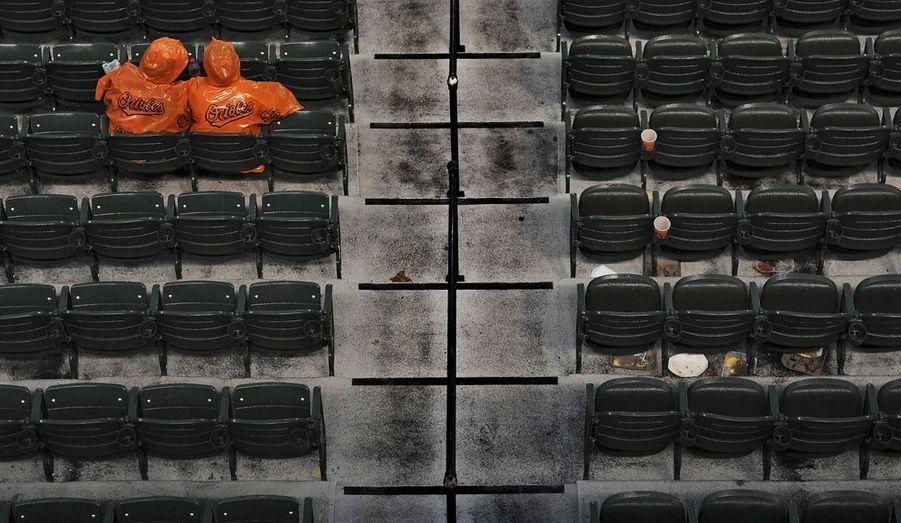 Ces deux supporters restent pour le match de baseball à venir entre l'équipe des Blue Jays et celles des Orioles, malgré la pluie.