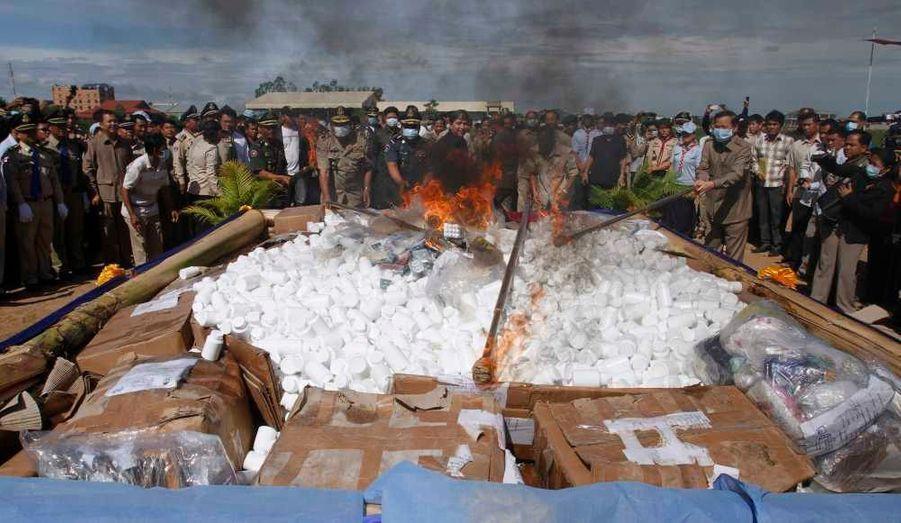 Des policiers et des badauds regardent des responsables du gouvernement cambodgien allumer le feu lors d'une opération de destruction de drogue saisie (dont la quantité est d'environ une tonne), à Phnom Penh.