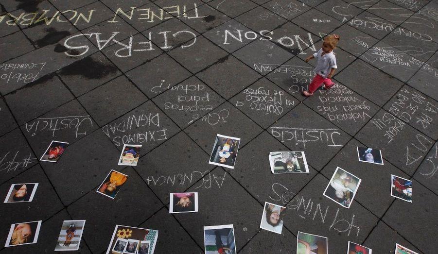 Une petite fille marche à côté de photographies des victimes d'un incendie à Guadalajara, au Mexique. Un homme armé a mis le feu à un casino jeudi dernier, faisant au moins 52 morts à Monterrey. Le président Felipe Calderon a déclaré trois jours de deuil national.