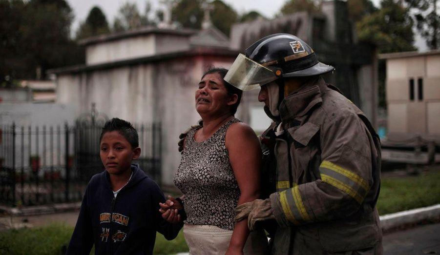 Une mère et son fils originaires du Guatemala pleurent dans les bras d'un pompier après que le pays a été victime d'une mini tornade dimanche.
