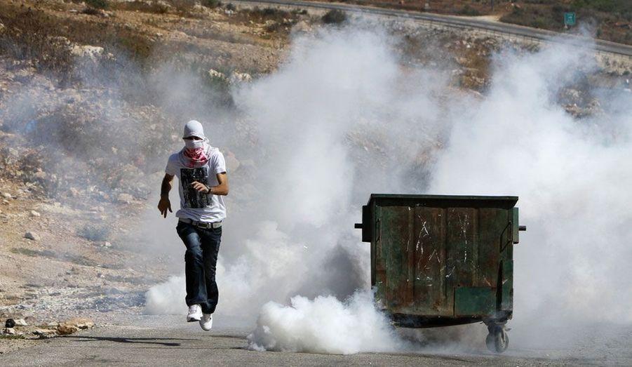 Un manifestant palestinien fuit les gaz lacrymogènes répandus par les forces israéliennes près d'une implantation de colons à proximité de Ramallah.