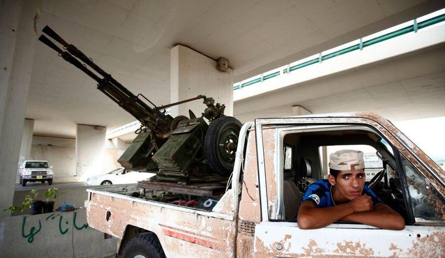 Un combattant anti-Kadhafi se tient dans un véhicule armé d'une mitrailleuse anti-aérienne tout près de l'aéroport de Tripoli.