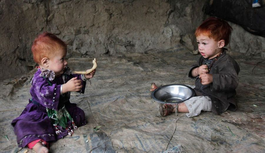 Deux enfants afghans déplacés dans un camp de réfugiés de Kaboul partagent ensemble le peu de nourriture qu'ils ont.
