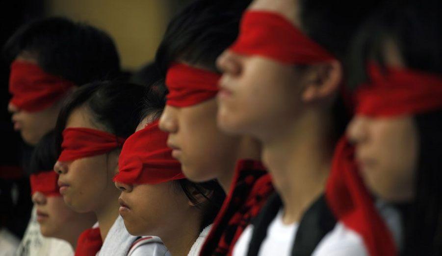"""Des étudiants se sont bandés les yeux afin de protester contre le nouveau programme qui va être mis en place à partir du 1er septembre dans les écoles chinoises. La colère se concentre sur un manuel de 34 pages, vantant le """"Modèle Chinois"""" et son parti unique, qui aurait permis une grande prospérité de la société et de l'économie du pays."""