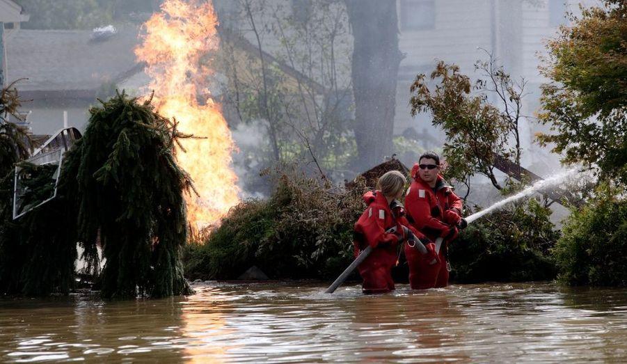 Des policiers du New Jersey (Etats-Unis) s'affairent à l'extinction d'un incendie causé par la rupture d'un conduit de gaz du fait de la crue d'une rivière à Pompton Lakes.