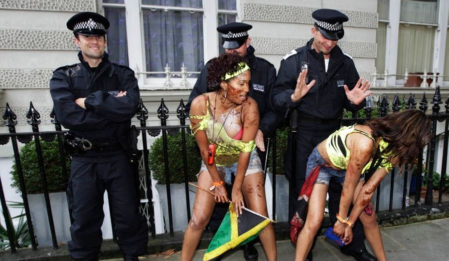 Deux femmes dansent devant des agents, durant le carnaval de Notting Hill. Suite aux émeutes, les effectifs policiers ont été renforcés à Londres dimanche.