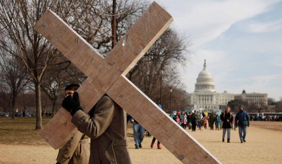 """Un militant anti-avortement porte un crucifix sur le Mall, l'esplanade en face du Capitole à Washington pendant l'annuelle """"Marche pour la vie"""", le 24 janvier. Comme à chaque anniversaire - 38e cette année - de la décision de justice Roe v. Wade, autorisant le droit à l'avortement, des milliers de personnes ont défilé devant la Cour suprême des États-Unis pour exprimer leur rejet de la loi."""