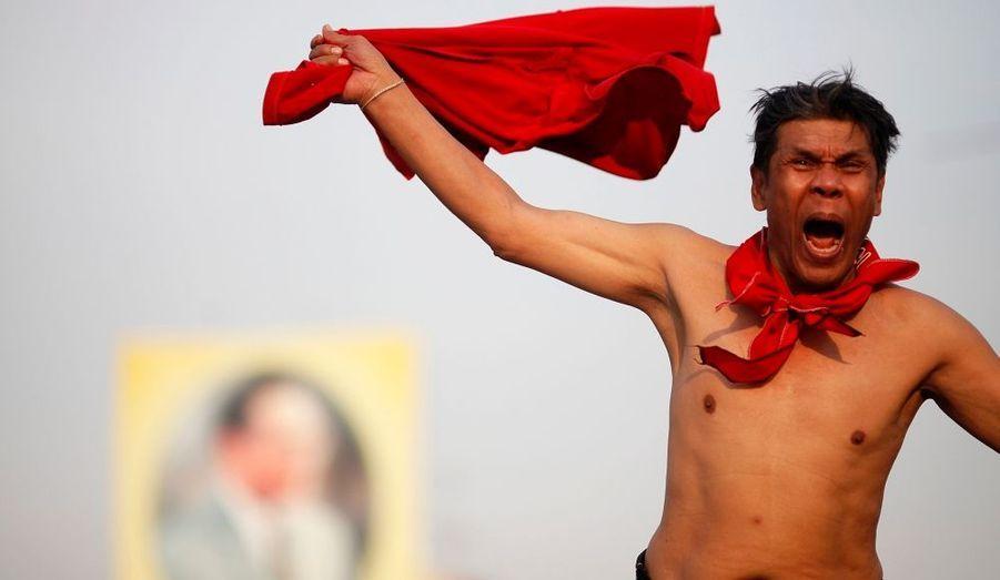"""Une """"chemise rouge"""", un manifestant anti-gouvernement, hurle lors d'un rassemblement à Bangkok, devant le monument de la Démocratie, théâtre d'affrontements sanglants avec les forces de sécurité, le 23 janvier. Un millier de militants anti-gouvernementaux se sont réunis dimanche dans la capitale thaïlandaise, pour exiger la libération de leurs dirigeants qui sont détenus depuis la répression de mai 2010."""