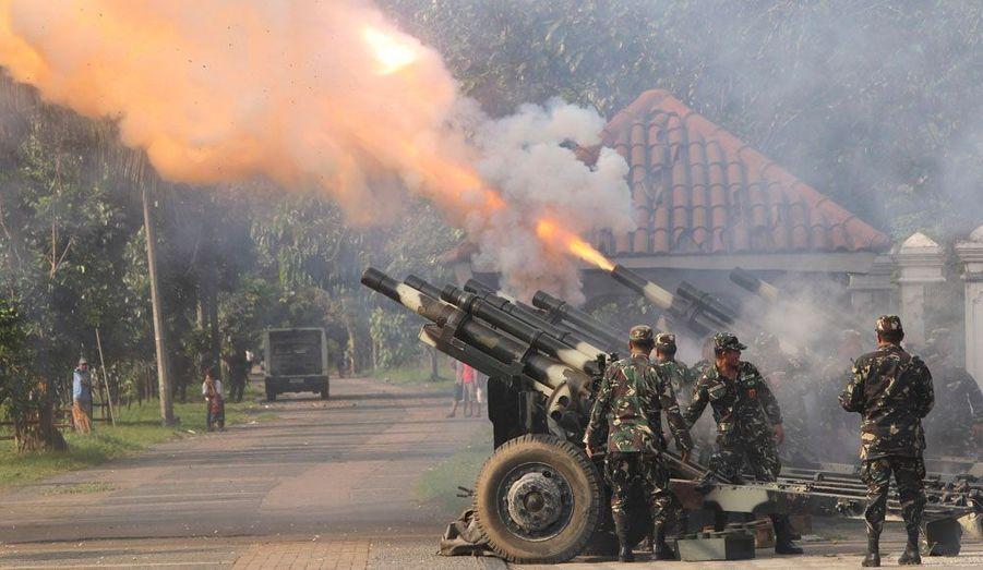 Ces soldats philippins ne pilonnent aucune cible, mais saluent l'arrivée du président Benigno Aquino lors d'une cérémonie à Manille.