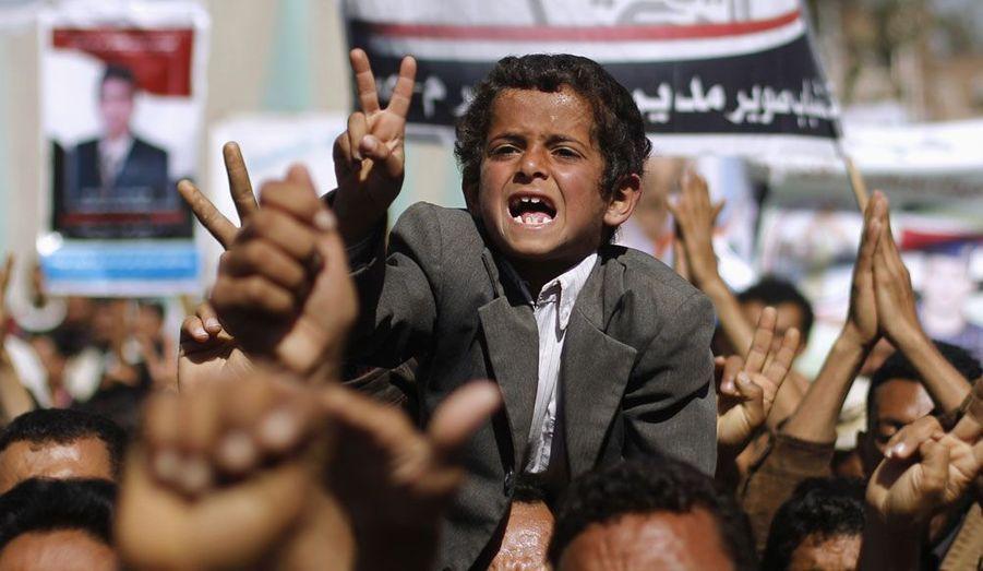 Un jeune garçon crie des slogans avec d'autres manifestants anti-gouvernementaux à Sanaa au Yémen. Ils réclament la libération de protestataires emprisonnés dans la ville.