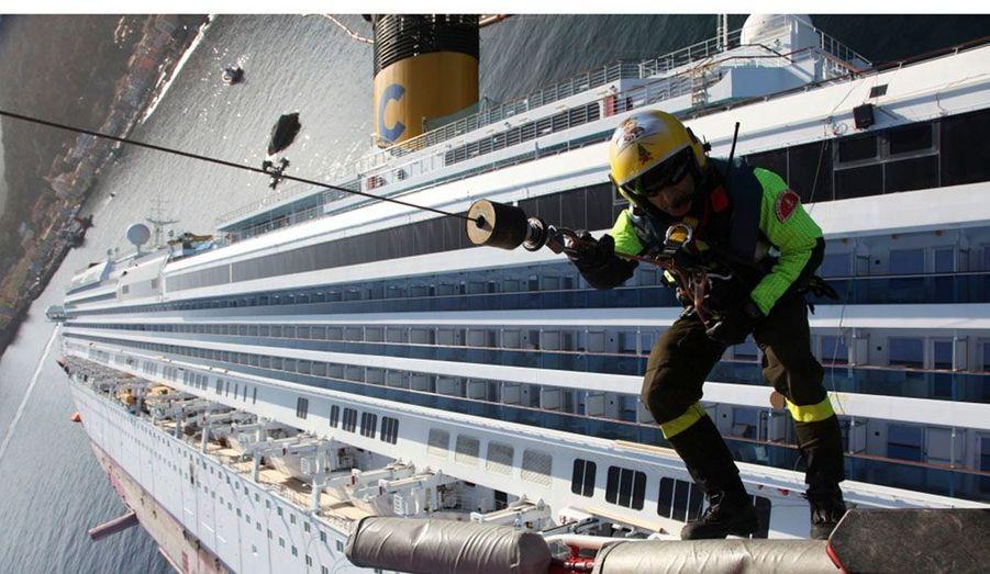 """Un pompier suspendu à un hélicoptère essaye de pénétrer dans le navire de croisière """"Costa Concordia"""" échoué au large de la côte ouest de l'Italie à l'île de Giglio."""