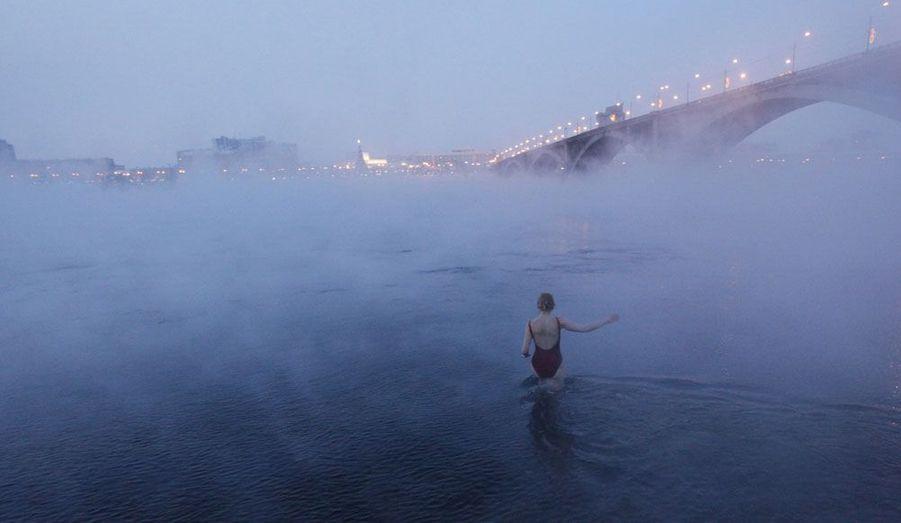 Une femme membre d'un club amateur de baignade d'hiver de Sibérie entre dans le fleuve Yenisei. A cette époque, la température extérieure descend régulièrement sous les 25 degrés.