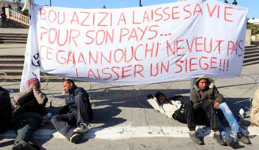 Plus d'une semaine après le départ du président Ben Ali, les manifestants tunisiens continuent de protester pour demander la démission de tous ses proches du nouveau gouvernement de transition, à commencer par celle du Premier ministre Mohamed Ghannouchi. Hier soir, ils ont continuer de camper devant son ministère en dépit du couvre-feu.