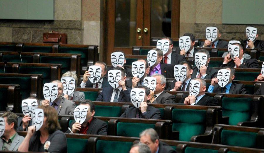 Les membres du parti polonais Ruch Palikota portent des masques lors d'une session de votes au Parlement pour montrer leur méfiance à l'égard du ministre de la Santé, Bartosz Arlukowicz.