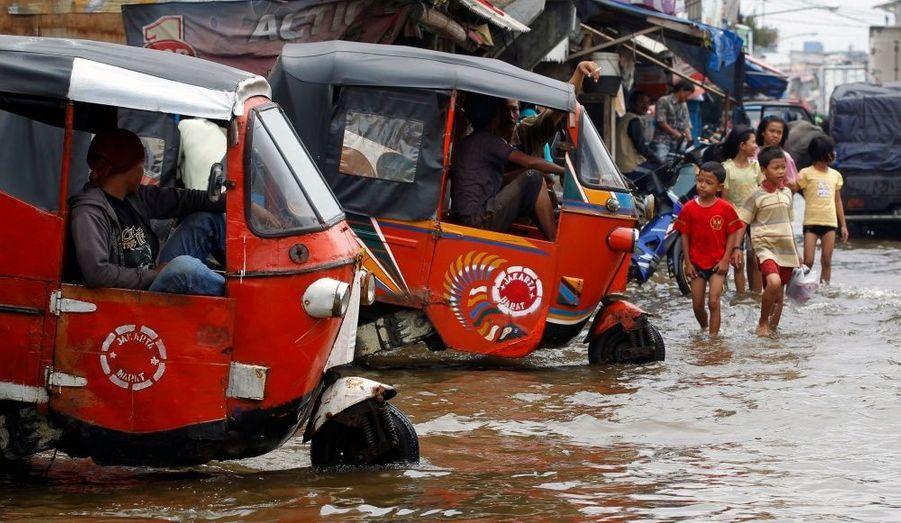 Des conducteurs de Bajaj, véhicules à deux roues, attendant des clients dans les rues inondées de Muara Baru, au nord de Jakarta.