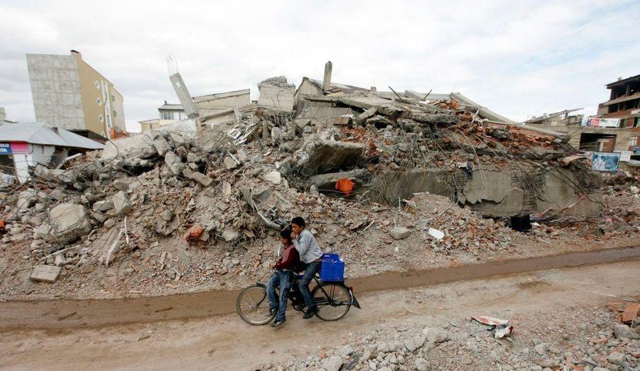 Deux enfants à vélo à Ercis, en Turquie. Le bilan du séisme s'est alourdi dimanche à 596 victimes. La veille, les secours ont cessé de chercher des survivants dans les décombres.
