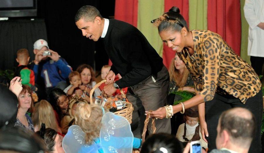 Michelle et Barack Obama donnent l'exemple en distribuant bonbons et friandises aux enfants à l'occasion d'Halloween.