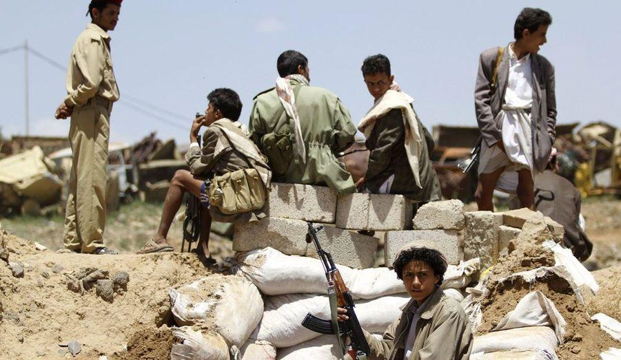 Un combattant tribal, fidèle à Mohammed Saleh al-Ahmar, commandant de l'armée de l'air démis de ses fonctions et demi-frère de l'ancien président du Yémen Ali Abdallah Saleh se tient devant avec d'autres militants prêts à reprendre le combat.